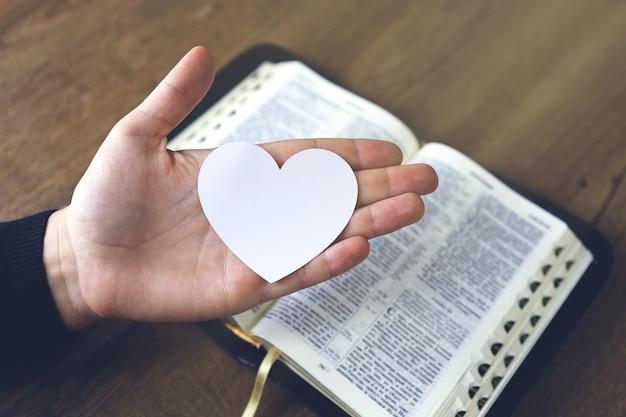 Mains femme prière à charger avec cœur brisé dans les mains sur la bible, concept prier pour la libération, le péché, pas de liberté.