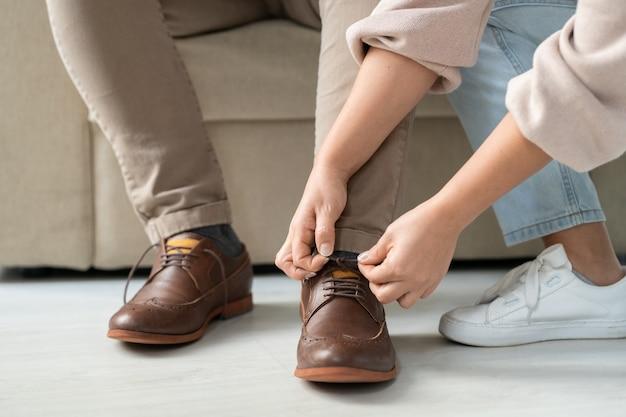 Mains de femme prudente aidant son père malade à nouer des lacets sur des bottes brunes avant de sortir