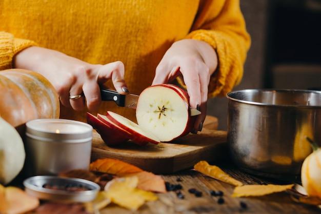 Mains de femme en pull jaune couper des pommes pour le vin chaud. ambiance de vacances confortable d'hiver