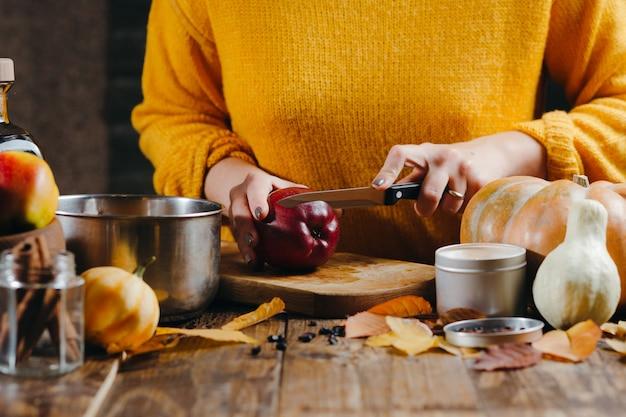 Mains de femme en pull jaune couper des pommes pour le vin chaud.