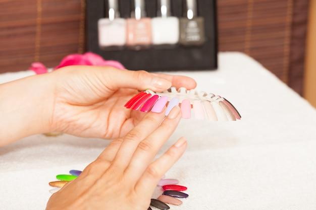 Mains d'une femme qui choisit la couleur de son vernis à ongles