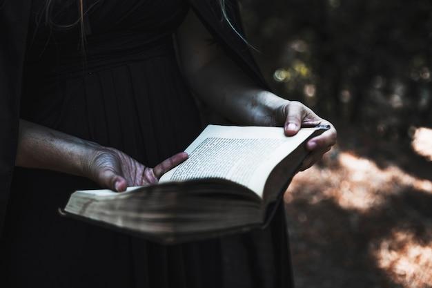 Mains de femme en robe noire et manteau tenant livre ouvert
