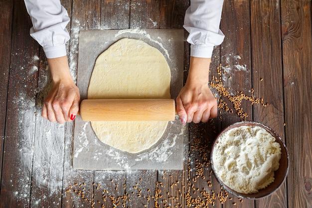 Les mains de la femme roulent la pâte
