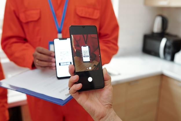 Mains de femme scannant le code qr sur un smartphone qui redirige sur le site web pour un paiement sans contact