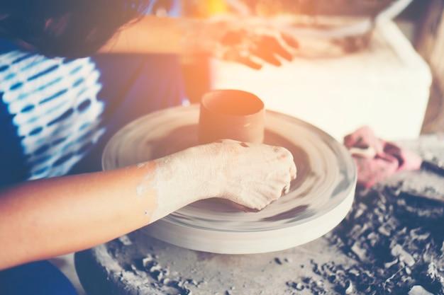Les mains de la femme se bouchent, le studio magistral de la céramique travaille avec de l'argile