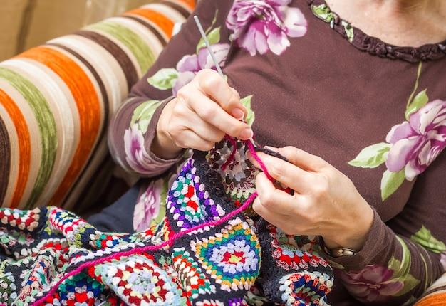 Mains de femme senior tricotant une courtepointe en laine vintage avec des patchs colorés