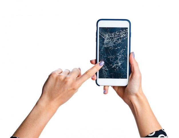 Mains de femme sur smartphone avec écran fissuré isolé sur blanc