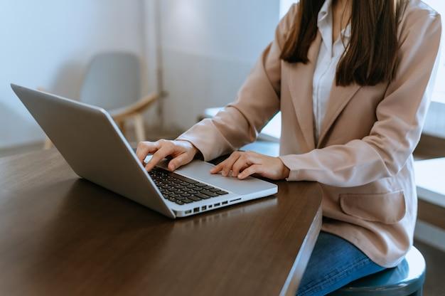 Les mains d'une femme tapent sur un ordinateur portable et tiennent une tablette au bureau