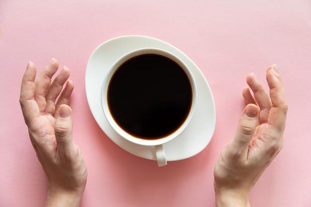 Mains de femme et une tasse de café sur fond rose, mise à plat