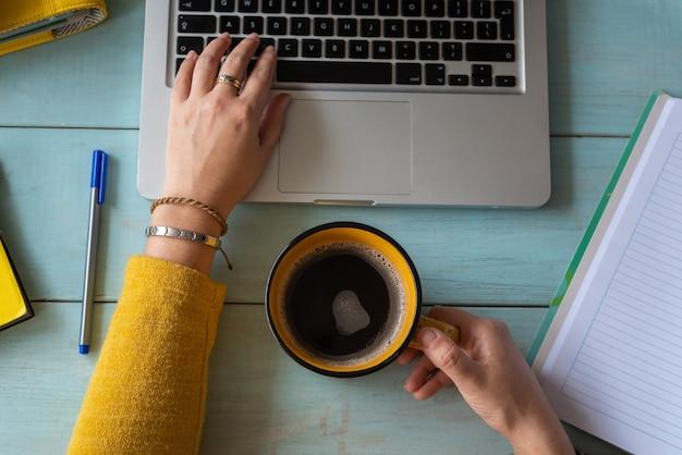 Les mains d'une femme avec une tasse de café ont travaillé sur son ordinateur portable. concept de travail à la maison.
