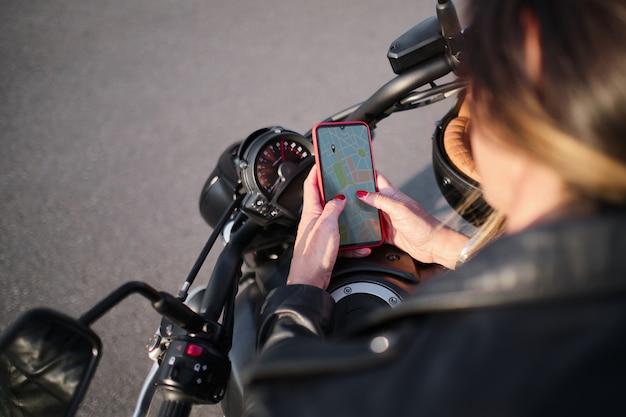 Les mains de la femme avec un téléphone intelligent sur un guidon de moto