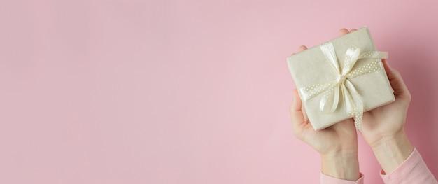 Mains de femme tenant une boîte-cadeau dans les palmiers sur bleu, bannière avec espace de copie