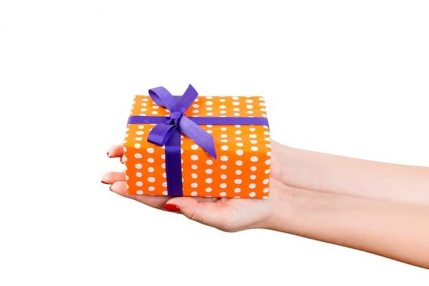 Mains de femme tenant une boîte cadeau emballée
