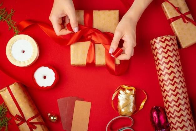 Mains de femme tenant une boîte de cadeau de noël sur un rouge