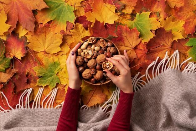 Mains de femme tenant un bol en bois avec des noix mélangées.