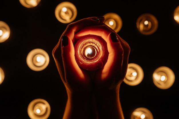 Mains de femme tenant une bougie allumée. de nombreuses flammes de bougies brillent. fermer.