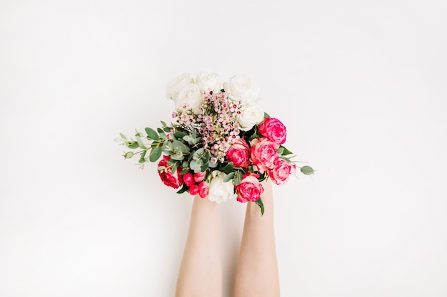 Mains de femme tenant un bouquet de fleurs de mariage avec des roses, une branche d'eucalyptus, des fleurs sauvages. mise à plat, vue de dessus