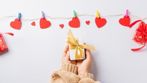 Mains de femme tenant un cadeau ou une boîte cadeau décorée et surprise coeur rouge