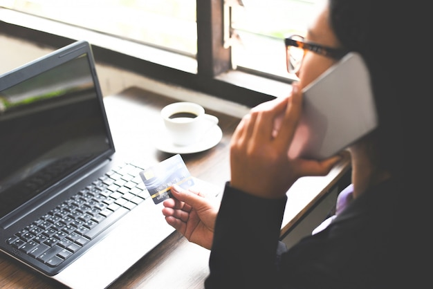 Mains de femme tenant une carte de crédit et utilisant un ordinateur portable et un téléphone portable pour faire des achats en ligne dans une table de bureau.