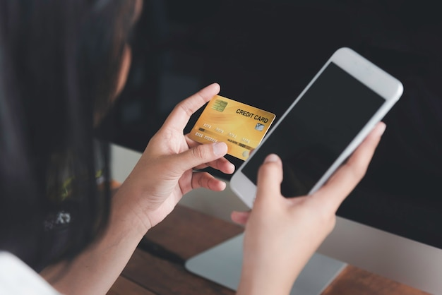 Mains de femme tenant une carte de crédit et utilisant un téléphone intelligent pour les achats en ligne ou le commerce électronique