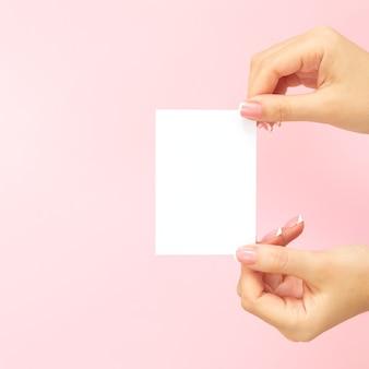 Mains de femme tenant une carte de visite blanche vierge, remise ou un dépliant sur fond rose