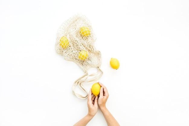 Les mains de la femme tenant le citron cru et le sac à cordes sur fond blanc. mise à plat, vue de dessus
