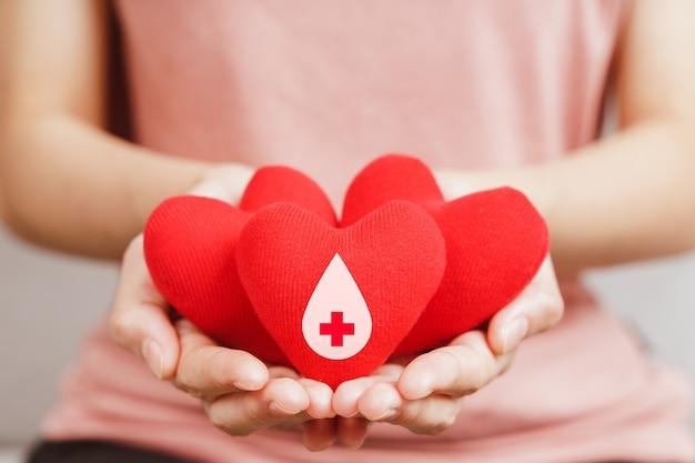 Mains de femme tenant un coeur rouge avec signe de donneur de sang. concept de soins de santé, de médecine et de don de sang