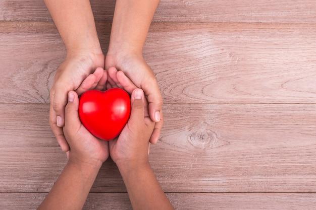 Mains de femme tenant coeur rouge et stéthoscope