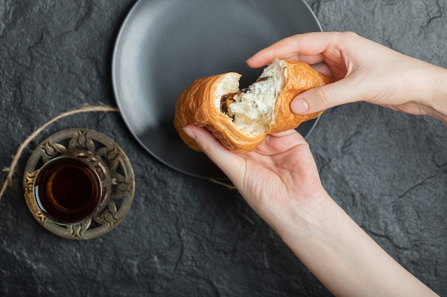Mains de femme tenant un croissant frais sur une plaque sombre.