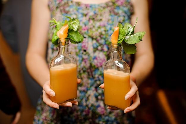 Mains de femme tenant deux bouteilles de verre avec cocktail alcoolisé