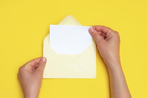 Mains de femme tenant une enveloppe ouverte avec carte blanche vierge