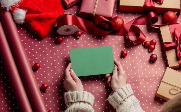 Mains de femme tenant une enveloppe verte sur du papier d'emballage
