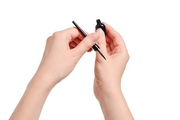 Mains de femme tenant un eye-liner isolé sur blanc