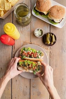 Mains de femme tenant des hot-dogs sur fond de bois