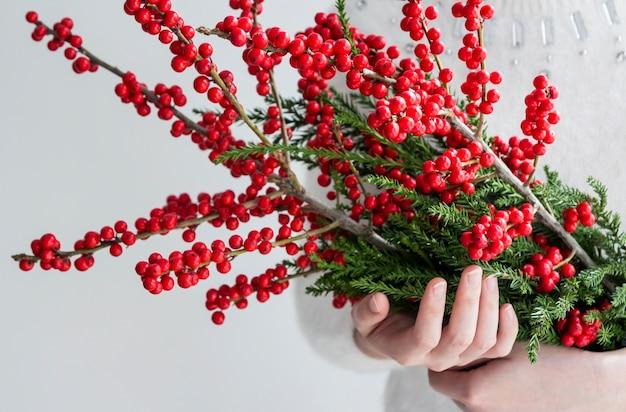 Mains de femme tenant ilex verticillata ou winterberry pour la décoration de noël