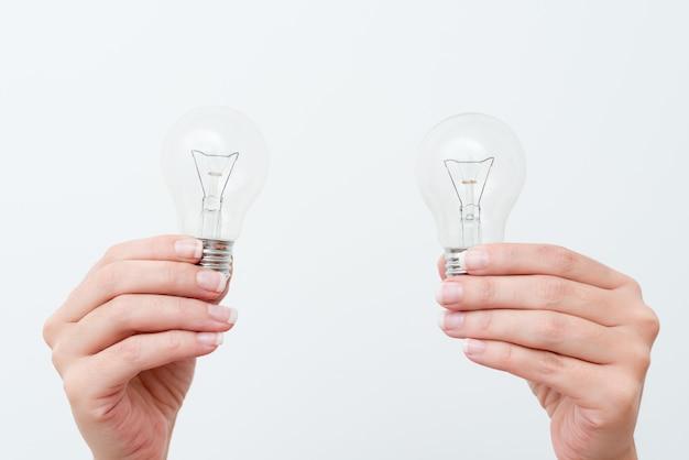 Mains de femme tenant une lampe présentant des idées de projet, paume de l'homme montrant des ampoules et de nouvelles technologies, deux ampoules tenues exposant une autre opinion.