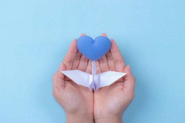 Mains de femme tenant un oiseau blanc et un coeur bleu. journée internationale de la paix.