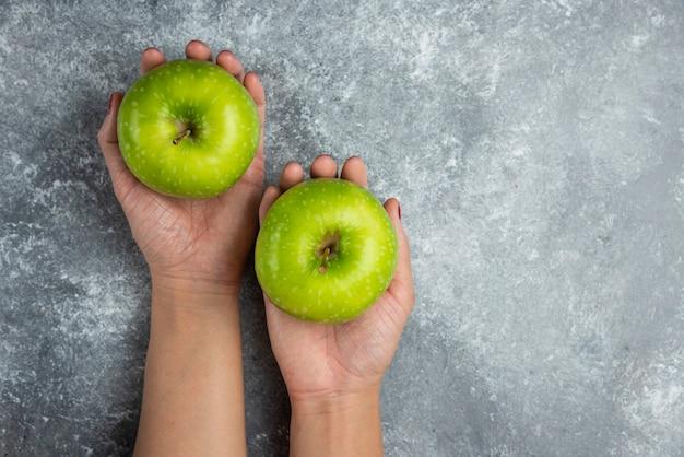 Mains de femme tenant des pommes vertes sur marbre.