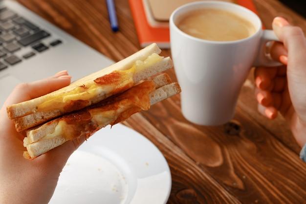 Mains d'une femme tenant un sandwich au-dessus de la table de travail avec ordinateur portable ouvert