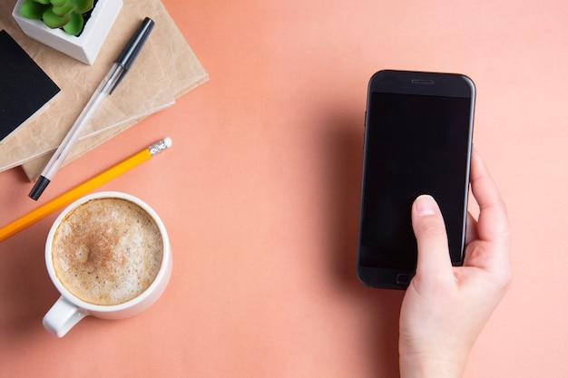 Mains de femme tenant un smarphone, une tasse de café. vue de dessus, espace de copie.