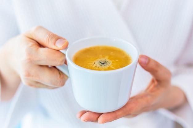 Mains de femme tenant une tasse de café chaud