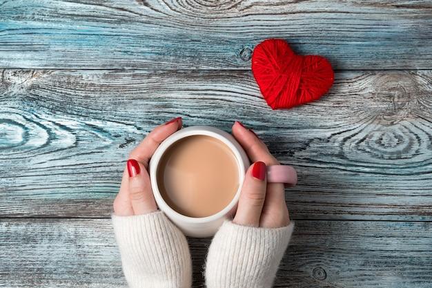Mains d'une femme tenant une tasse de café avec du lait sur un fond romantique.