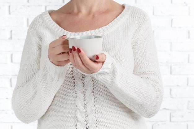 Mains de femme tenant une tasse de café