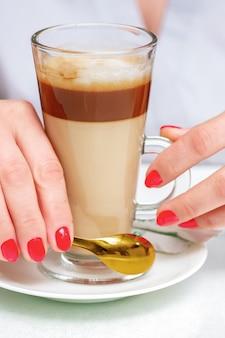 Mains de femme tenant une tasse de cappuccino de café avec une manucure rouge parfaite, gros plan.