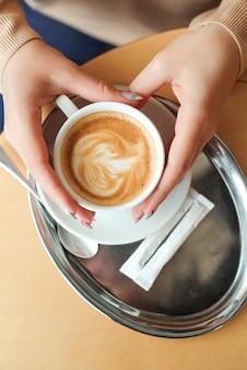Mains de femme tenant une tasse de cappuccino