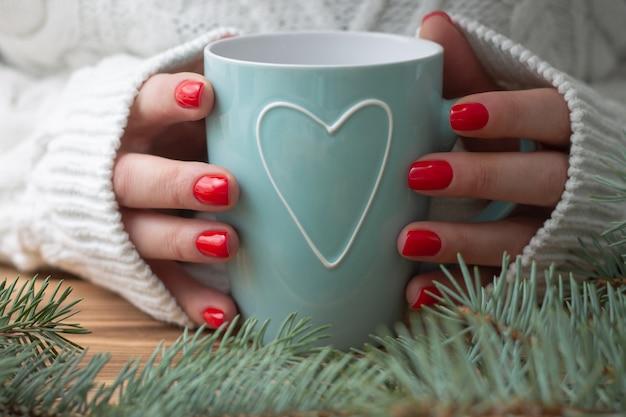 Mains de femme tenant une tasse de menthe