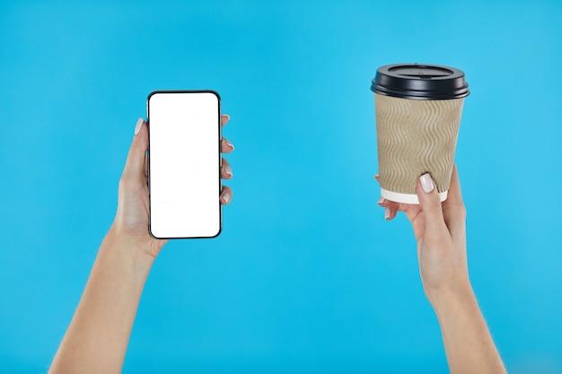 Mains de femme tenant la tasse de papier café et smartphone sur un bleu.