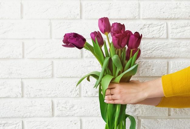 Mains de femme tenant des tulipes sur le fond du mur de briques