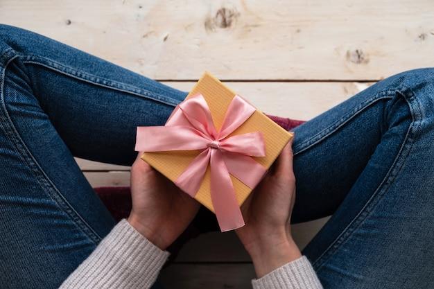 Mains de femme tenir la boîte-cadeau avec ruban rose sur une surface claire