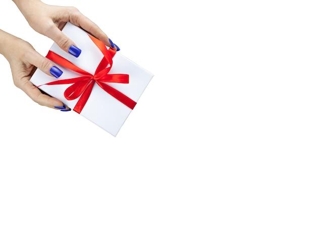 Mains de femme tiennent la boîte cadeau de couleur blanche avec ruban rouge pour la vue de dessus isolée sur le tableau blanc. gros plan, vue de dessus. flou sélectif. espace de copie de texte. concept de vacances
